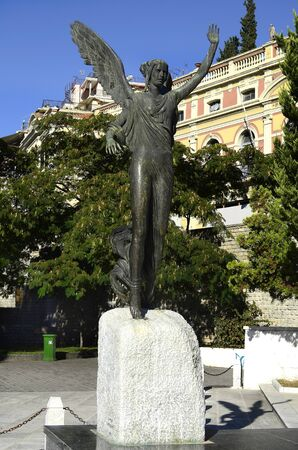 nike: Kavala, Greece - statue of Godess Nike, the bronze statue of victory is in the Iroon public garden and was made by sculptor John Parmakelis, in background the Megali Leschi building