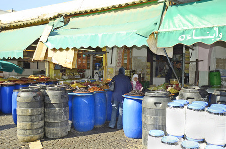 general store: Casablanca, Morocco - November 18th 2014: Unidentified people in traditional kaftan and shop with different olives in the souk of the city