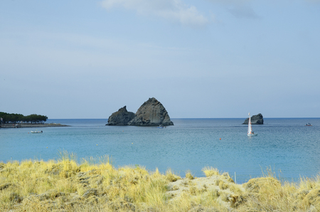 watersports: Myrina, Lemnos - September 21st 2015: Unidentified people in sailing boat and tiny rock island in aegean sea