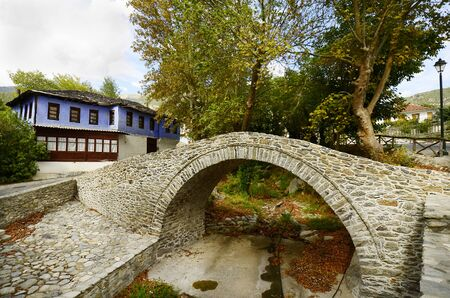 pedestrian bridge: Greece, footbridge over river bed and colorful home in mountain village Moustheni
