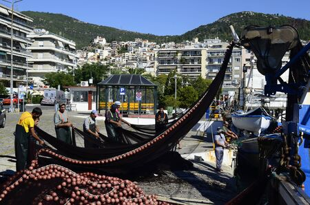 arbeit: KAVALA, GREECE - SEPTEMBER 23: fishermen in the harbour of the city preparing their nets for next ride, a daily routine in a hard business on the sea Editorial