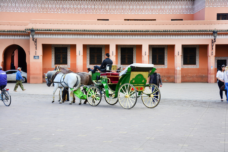 mode transport: Marrakesh, Morocco - November 22nd 2014: Unidentified people and horse drawn coach, traditional mode of transport and tourist attraction Editorial