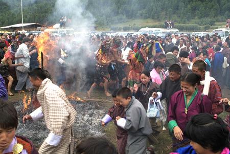 buddhismus: Glaeubige laufen durch die brennenden Reisighaufen beim Feuerfest beim Thangbi Lhakhang im Choekhor Tal bei Jakar (Chakhar)