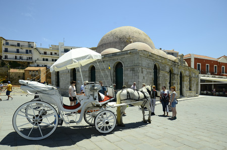pascha: Chania, Greece - May 27th 2014: Unidentified people and horse drawn coach in front of Janissaries mosque aka Hassan Pascha mosque in the harbor of the medieval village in Crete