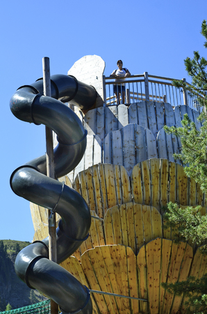 preferred: Jerzens, Austria - June 24th 2016: Woman in Zirbenpark, preferred playground and lookout with spiral slide in hiking area Hochzeiger mountain Editorial