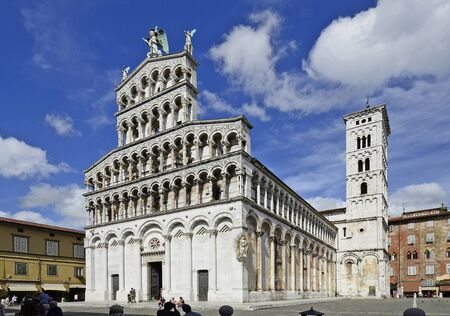san michele: Lucca, Italy - June 11th 2012: church San Michele in Foro with sculpure of Holy Michel on Top and the bell tower