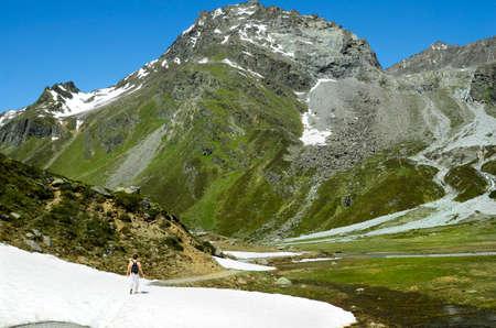 Austria, Tirol, woman on hiking trail over snow field in Austrian Alps