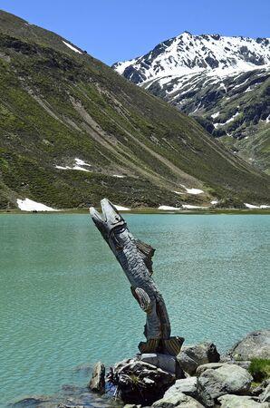 tirol: Austria, Tirol, fish sculpture made from tree trunk on Rifflsee lake in Austrian alps Stock Photo