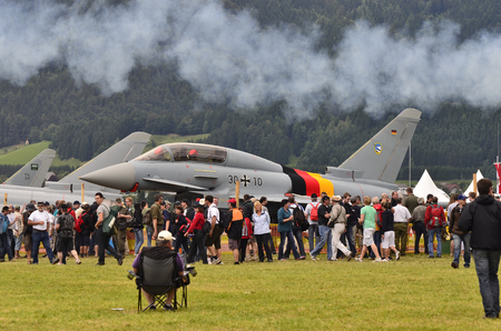 airpower: Zeltweg, Austria - July 1st 2011: Crowd of spectators by public airshow - named airpower11 on airfield Hinterstoisser with Typhoon airchraft aka Eurofighter of German army Editorial