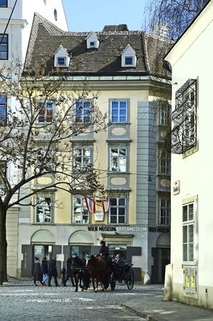 coachman: Vienna, Austria - March 27th 2016: Unidentified people and coachman in horse drawn coach named Fiaker, traditional kind of transport for sightseeing in the inner city