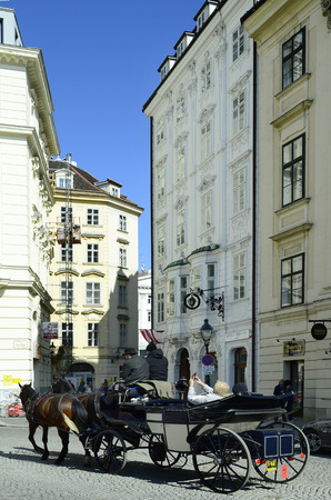 preferred: Vienna, Austria - March 27th 2016: Unidentified tourists by sightseeing in traditional horse drawn coach named Fiaker, a preferred tourist attraction