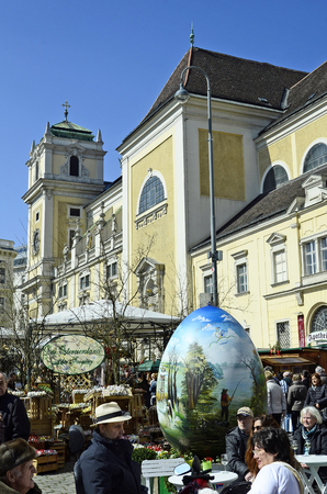 giant easter egg: Vienna, Austria - March 27th 2016: Unidentified people and arful decorated giant easter egg on traditional Easter market on Freyung square with church of Scottish monastery aka Schottenkirche Editorial