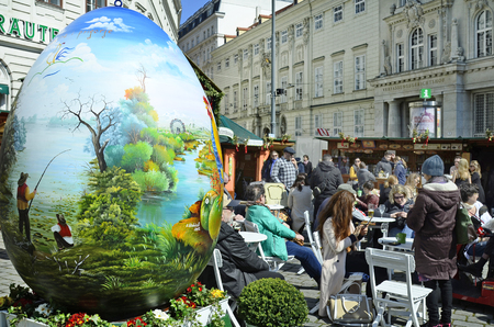 giant easter egg: Vienna, Austria - March 27th 2016: Unidentified people and arful decorated giant easter egg on traditional Easter market on Freyung square