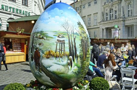 giant easter egg: Vienna, Austria - March 27th 2016: Unidentified people, shops and artful decorated giant easter egg on traditional Easter market on Freyung square