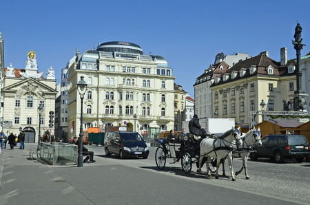 tourist attraction: Vienna, Austria - March 27th 2016: Unidentified tourists by sightseeing in traditional horse drawn coach named Fiaker on Am Hof square, a preferred tourist attraction