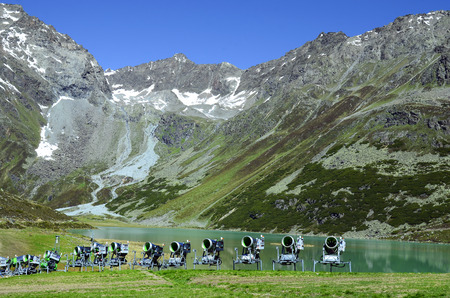 Austria, Tirol, snow cannons in front of Rifflsee lake in Tyrolean Alps Stock Photo