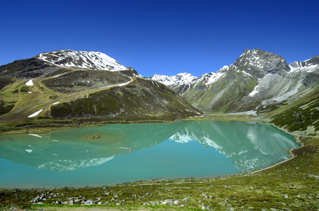 Austria, Tirol, Rifflsee - lake and snow remains in Tyrolean Alps, preferred area for skiing and hiking