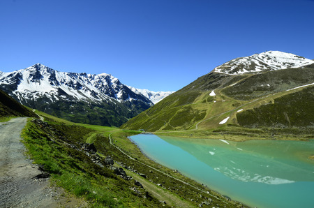 preferred: Austria, Tirol, Rifflsee - lake and snow remains in Tyrolean Alps, preferred area for skiing and hiking