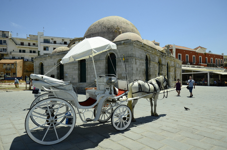 pascha: Chania, Greece - May 27th 2014: Unidentified people and horse drawn coach in front of the Janissaries mosque at the harbor of the medieval village in Crete