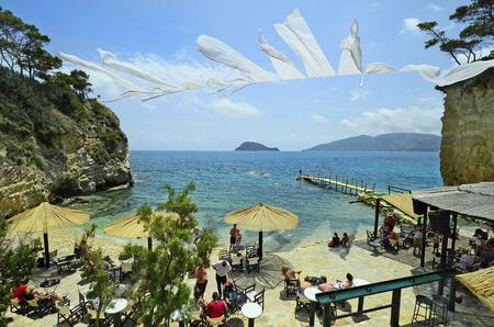 Zakynthos, Griechenland - 24. Mai 2016: Unidentified Menschen am Strand von winzigen Miniatur-Insel mit Bar und Badesteg, Marathonissi Insel aka Turtle Insel im Hintergrund Standard-Bild - 67532608