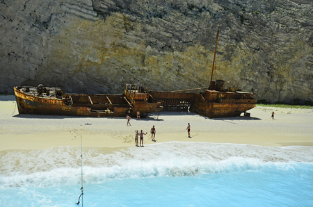 Zakynthos, Greece - May 25th 2016: Unidentified people and wreck of stranded vessel on shipwreck beach, preferred travel destination and landmark on the island in Ionian sea