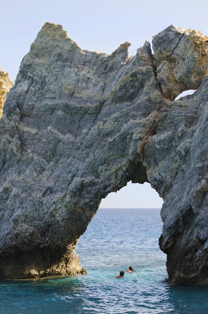 reachable: Skiathos, Greece - October 3rd 2012: unidentified people enjoy the clear sea, swimming through the rockhole named Tripia Petra on Lalaria beach - one of the landmarks of the island which is reachable only by boats