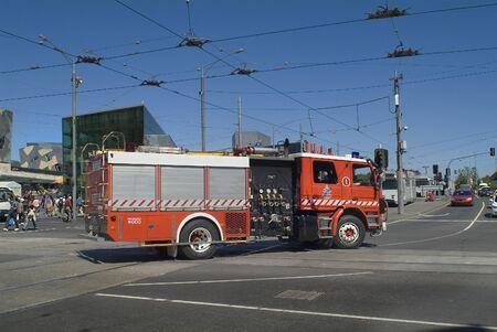 fire brigade: Melbourne, Australia - November 9, 2006: Unidentified people and fire brigade vehicle crossing Flinders street Editorial