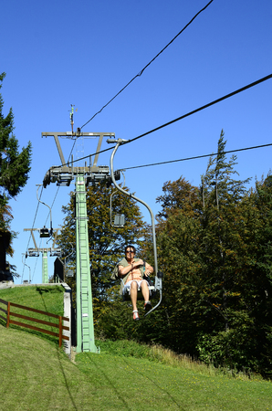 chair on the lift: Lilienfeld, Lower Austria - September 30, 2016: Unidentified woman on chair lift to Muckenkogel mountain