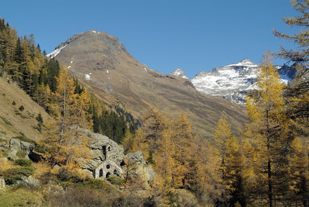Austria, little chapel built in rock and autumn forest in Gschloess-Valley, Stock Photo