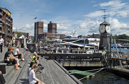 oslo: Oslo, Norway - June 21, 2009: Unidentified people and ships on Aker Brygge with townhall in background