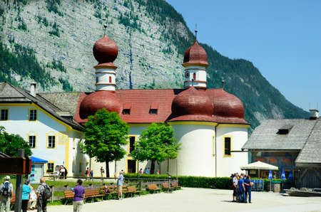 reachable: St. Bartolomew, Germany - June 12, 2015: Unidentified tourist on sightseeing of the little church on Koenigssee lake, preferred tourist attraction and landmark in Bavaria, reachable only by boat Editorial