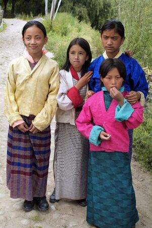 religious clothing: Jakar, Bhutan - September 26, 2007: Unidentified children in traditional clothing named Kira and Kho on way to religious ceremony