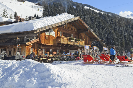 Saalbach, Austria - February 18, 2013: Unidentified people relax and enjoy a sunny winter day on mountain inn in ski resort Saalbach-Hinterglemm in Salzburg