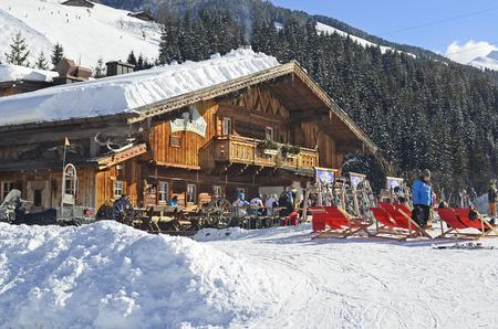 Saalbach, Austria - February 18, 2013: Unidentified people relax and enjoy a sunny winter day on mountain inn in ski resort Saalbach-Hinterglemm in Salzburg