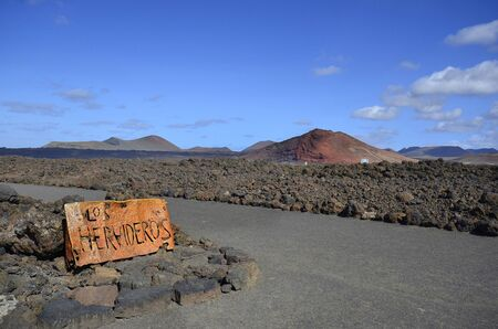 spain, desert landscape with sign to natural spectacle and tourist attraction Los Hervideros on Lanzarote