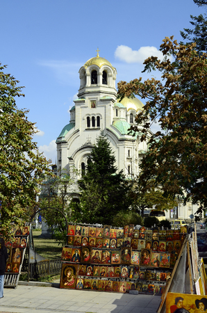 Sofia, Bulgaria - September 25th 2016: Icons on weekly second hand street market and Aleksandar Nevski cathedral behind Editorial