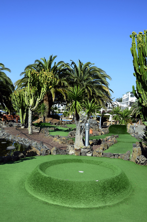 Fuerteventura, Spain - March 29, 2017: Hole of mini golf court imidst tropical vegetation of a hotel complex