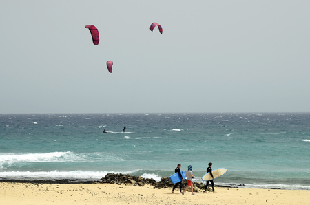 Fuerteventura, Spain - March 31, 2017: Unidentified sporty people on beach on Canary island, preferred destination for surfer and kiter