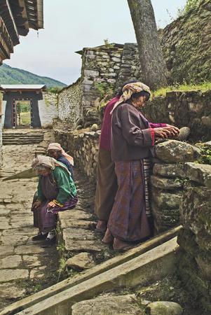 Jakar, Bhutan - September 26, 2007: Unidentified elder woman in traditional dress prepare snack with betelnut -  named Doma - a traditional drug in Bhutan
