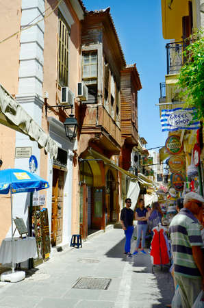 Rethymno, Greece - May 22nd 2014: Unidentified people in narrow street with shops, restaurant, pub and homes with Turkish balcony