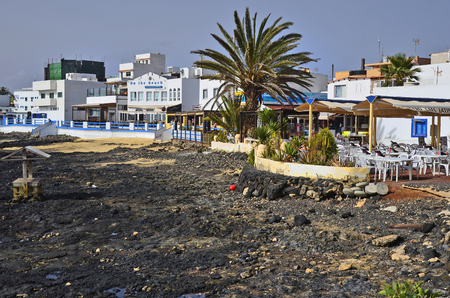 Corralejo,  Fuerteventura, Spain - April 02, 2017: Unidentified people and restaurants on promenade with rocky beach  in the city on Canary Island