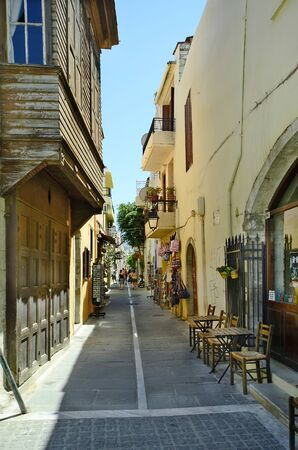 Rethymno, Greece - May 22nd 2014: Unidentified people in small street with shops and homes with Turkish balcony
