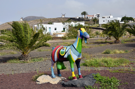 Villaverde, Fuerteventura, Spain - April 01, 2017: Colorful goat sculpture and windmills in the rural village on Canary Island