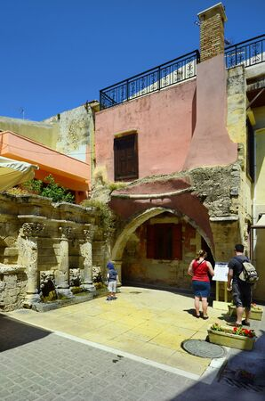 Rethymno, Greece - May 22nd 2014: Unidentified people in front of landmark Raimondi fountain and colorful home in the medieval city in Crete
