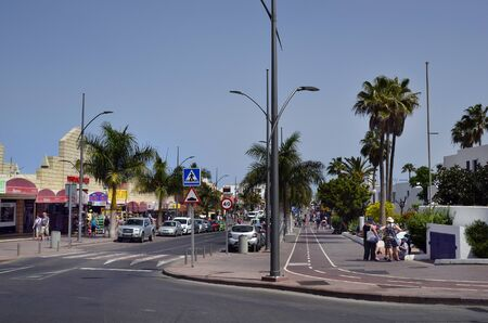Corralejo,  Fuerteventura, Spain - April 02, 2017: Unidentified people and different shops on main street in the city on Canary Island