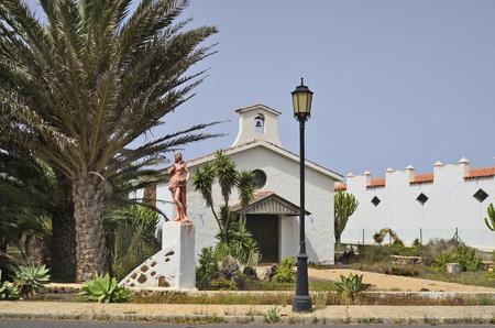 La Oliva, Fuerteventura, Spain - April 01, 2017: Female sculpture and chapel named Hermita en La Oliva in the tiny village on Canary island