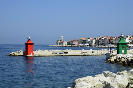 Piran, Slovenia - July 4th 2015: Unidentified people on harbor entrance, restaurants, buildings and medieval church Sveti Klementa in the pictureske village on Adriatic sea