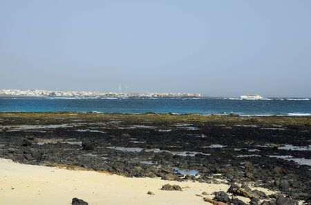 Corralejo, Fuerteventura, Spain - March 31, 2017: Rocky coast and ferry boat with view to Corraleja village Editorial