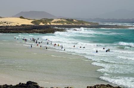 Fuerteventura, Canary Island, Spain - March 31, 2017: Unidentified surfers on beach Playa de Corralejo Editorial