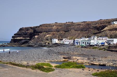 El Puerte de Los Molinos, Fuerteventura, Spain - April 01, 2017: Unidentified people on beach, restaurant and homes on west coast of the Canary island